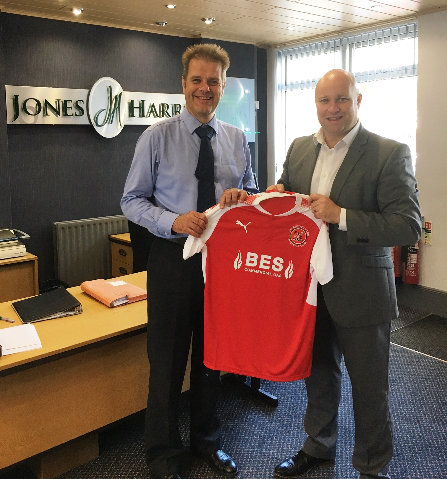 Head of Commercial Martin Booker shakes hands on extending the partnership with Martin Wigley at Jones Harris Accountants premises on St Peters Square Fleetwood.
